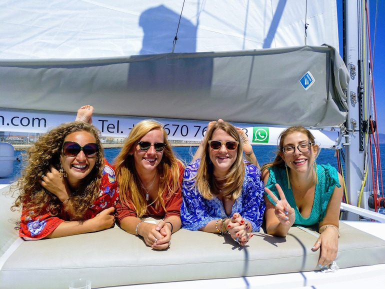 happy girls soaking up the sun on a sail barcelona experience with wanderbeak tours